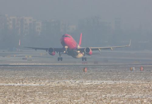 Startujący Wizzair i w tle, tonący w smogu Ursynów, na codzień dosyć widoczny z drugiej strony Lotniska.
